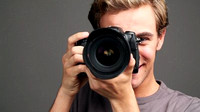 stock-footage-young-man-photographer-taking-photographs-with-digital-slr-camera